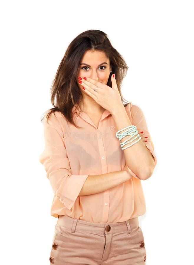Förvånad kvinna som använder handen för att täcka munnen arkivfoto