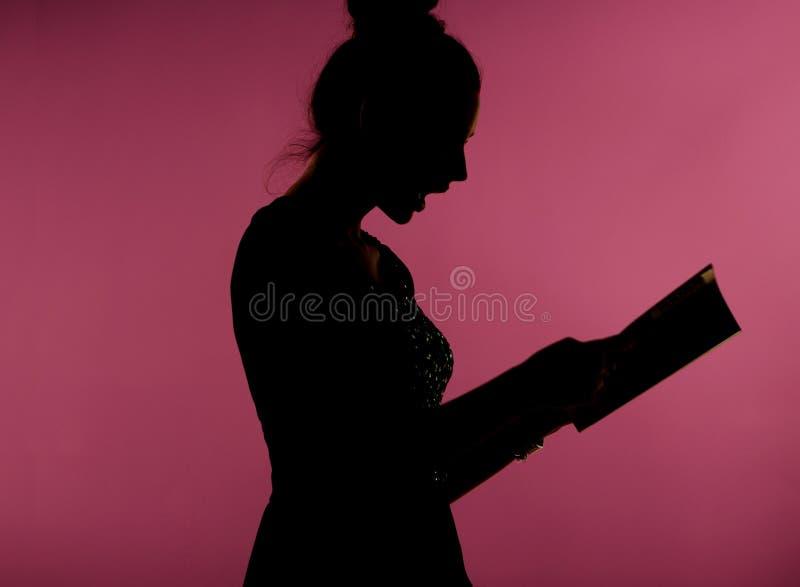 Förvånad kvinna som läser tidskriften arkivbild