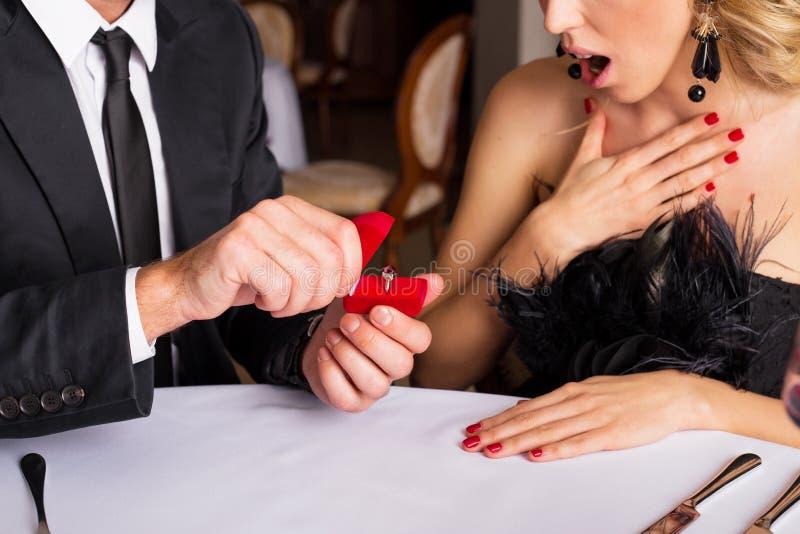 Förvånad kvinna som ser förlovningsringen royaltyfri bild