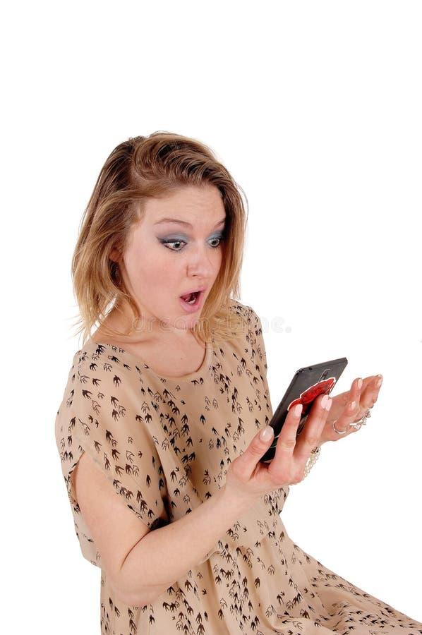Förvånad kvinna som ser hennes mobiltelefon royaltyfria foton
