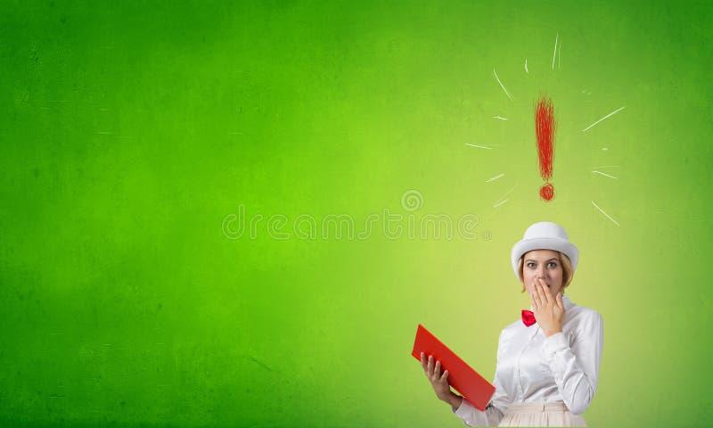 Förvånad kvinna som ser i bok arkivbilder