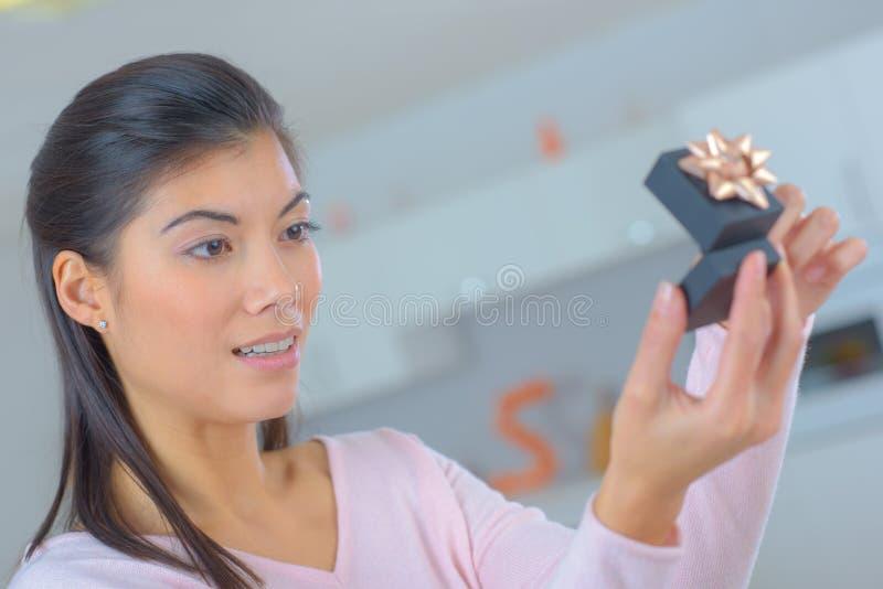 Förvånad kvinna som ser på asken med vigselringen royaltyfria bilder