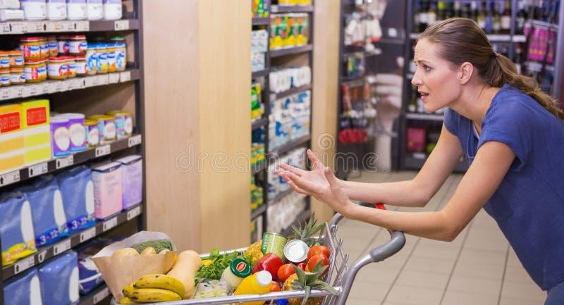 Förvånad kvinna som ser produkten på hylla royaltyfria bilder
