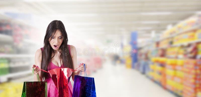 Förvånad kvinna som ser shopping arkivfoton