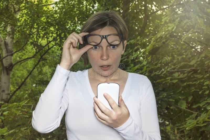 Förvånad kvinna som ser telefonen arkivfoton