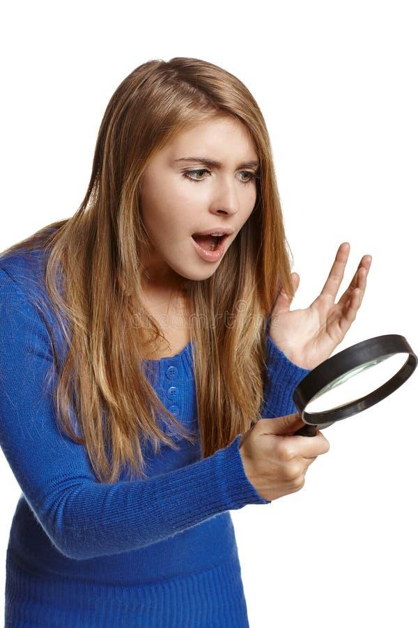 Förvånad kvinna som ser till och med förstoringsglaset arkivbilder