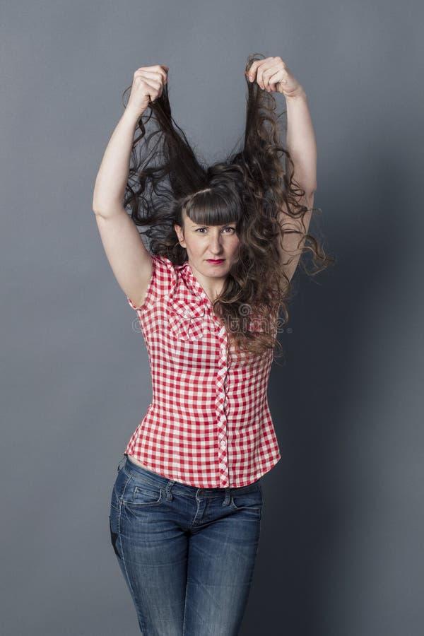Förvånad kvinna som ut drar hennes långa lockiga bruna hår royaltyfri bild