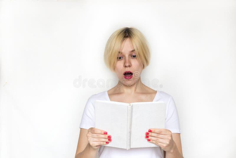 Förvånad läsebok för ung kvinna arkivfoton