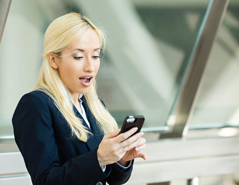Förvånad läsning för affärskvinna något på hennes smarta telefon royaltyfri bild