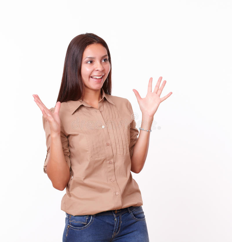 Förvånad latinamerikansk flicka med brunt blusanseende arkivfoto