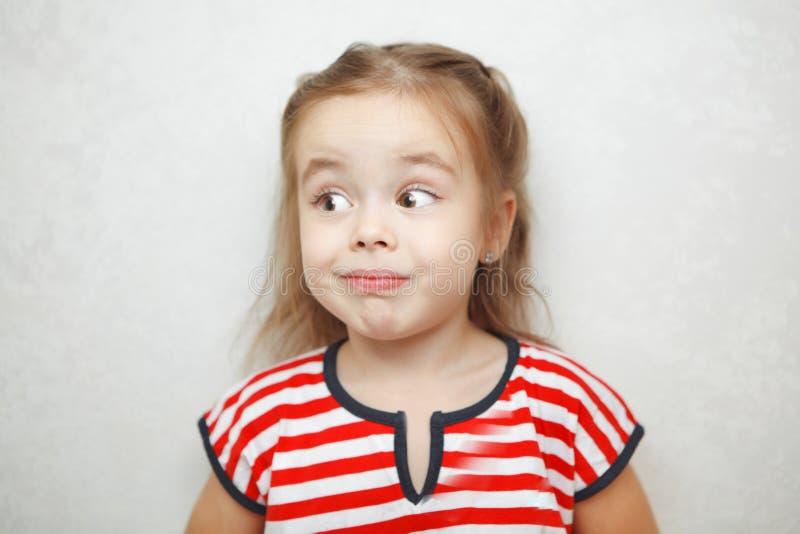 Förvånad liten flicka med det välvda ögonbrynståendefotoet royaltyfri bild