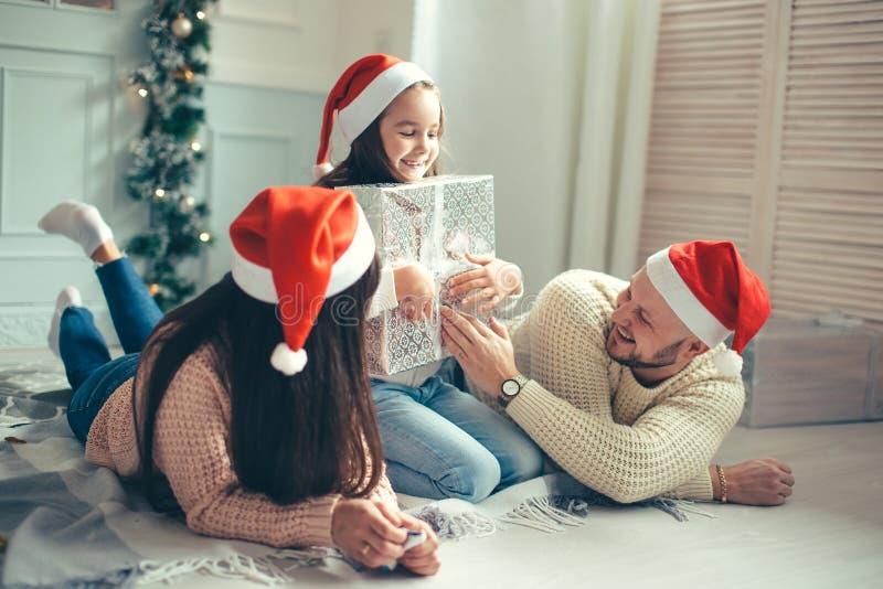 Förvånad liten flicka med julgåvor nära en julgran hemma royaltyfria foton
