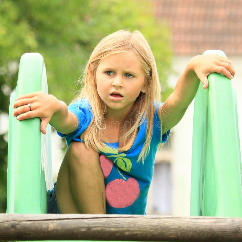 Förvånad liten flicka på en glidbana arkivfoton