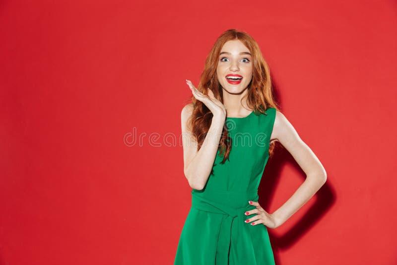 Förvånad lycklig kvinna i grön klänning med armen på höft royaltyfria bilder