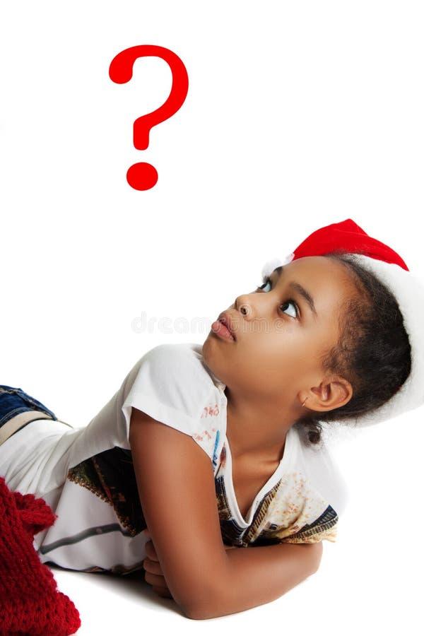 Förvånad mörkhyad tonårig flicka Flickan i hatten av jultomten fotografering för bildbyråer
