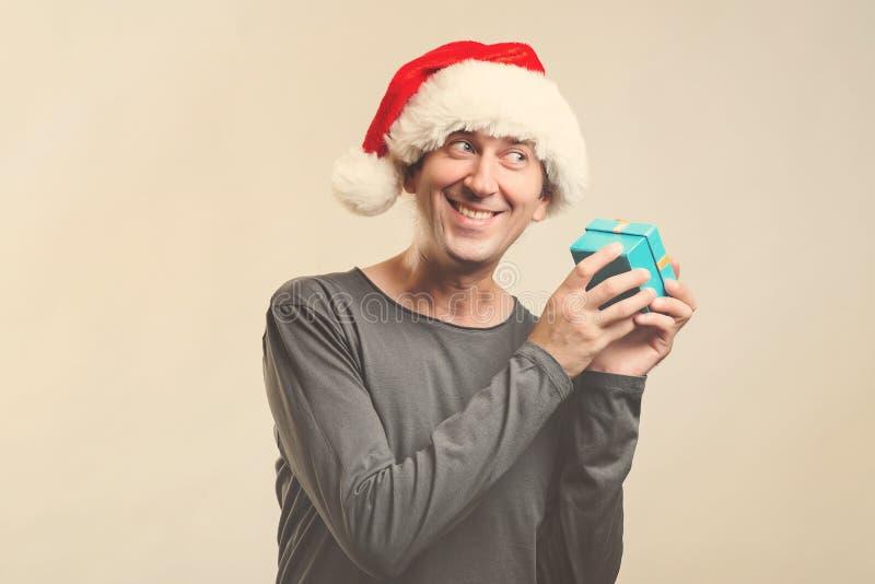 Förvånad man i ask för gåva för jultomtenhattinnehav Jultomtenjulman som isoleras på vitt, kopieringsutrymme lycklig flicka med l arkivbilder