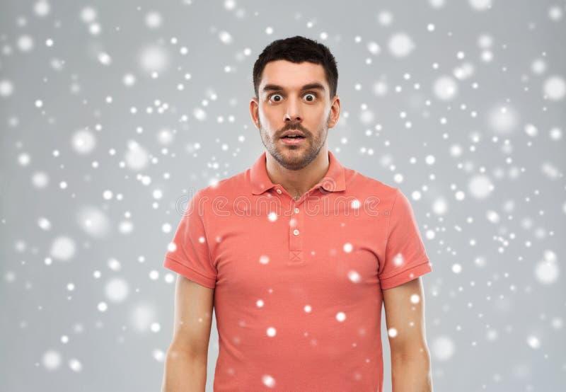 Förvånad man i polot-skjorta över snöbakgrund royaltyfria foton