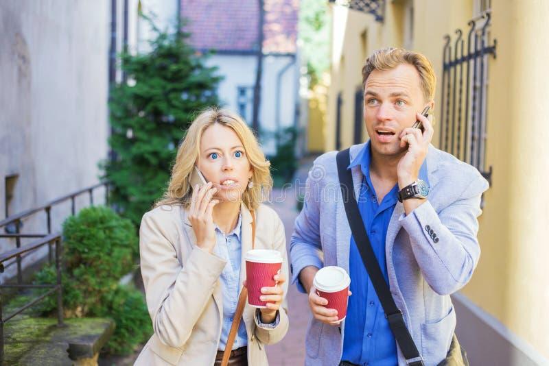 Förvånad man och kvinna som talar på telefonen royaltyfria bilder