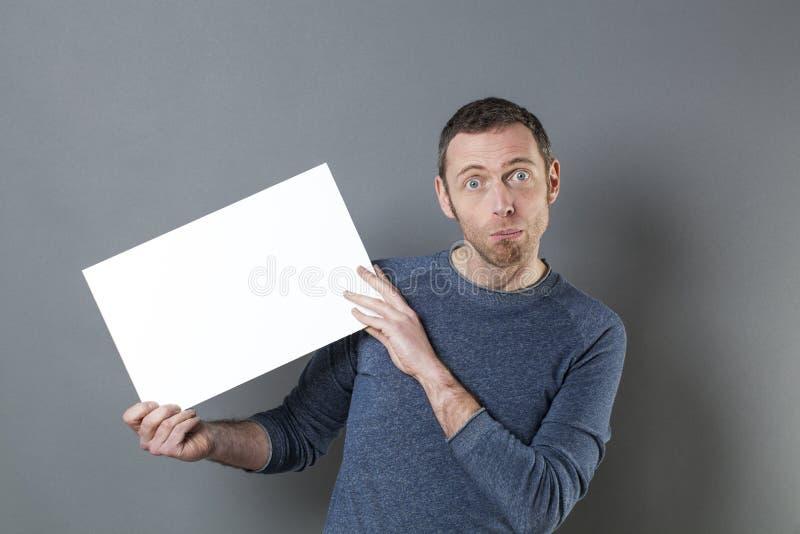 Förvånad man som framlägger det tomma kortet för din annons arkivfoto