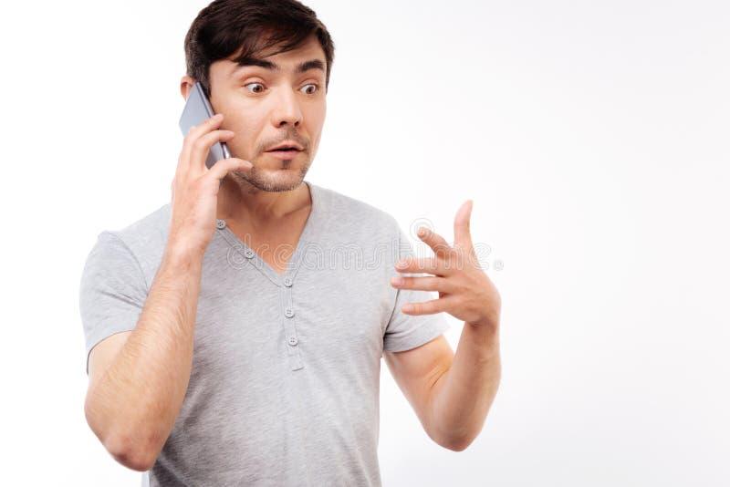 Förvånad man som lyssnar till chockerande nyheterna på telefonen arkivbilder