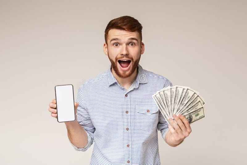 Förvånad millennial grabb med pengar och mobiltelefonen arkivbild