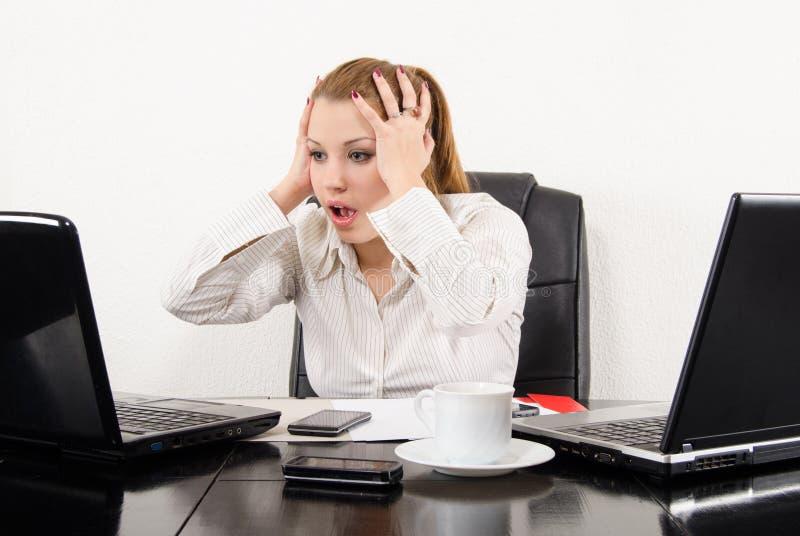 Förvånad multitasking för affärskvinna royaltyfri foto
