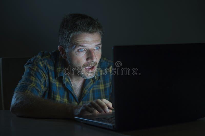 Förvånad och chockad man på natten som arbetar med bärbar datordatoren i mörkret, i att hålla ögonen på för misstro- och överrask arkivfoton