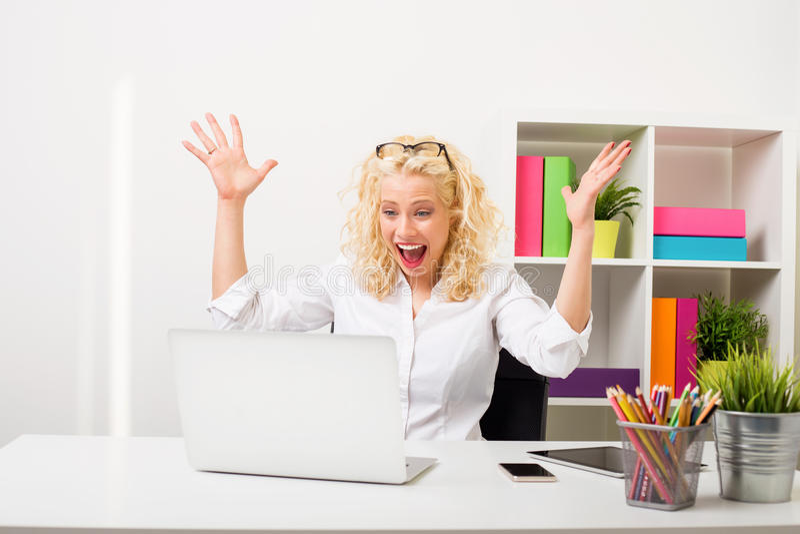 Förvånad och lycklig kvinna på kontoret som visar hennes spänning royaltyfri bild