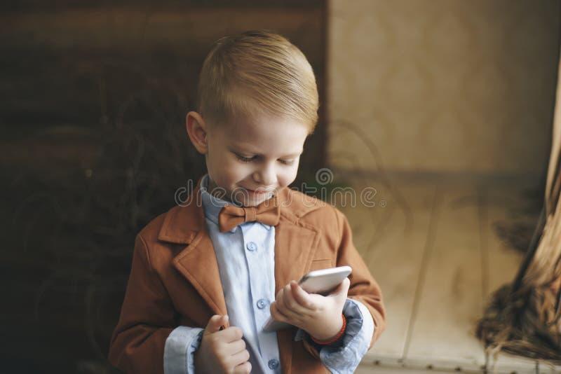 Förvånad pojke med smart klockasammanträde på terrass och användamobiltelefonen royaltyfria foton