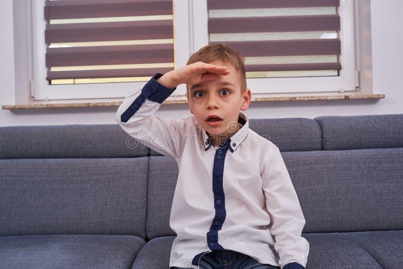Förvånad pojke på soffan royaltyfri bild