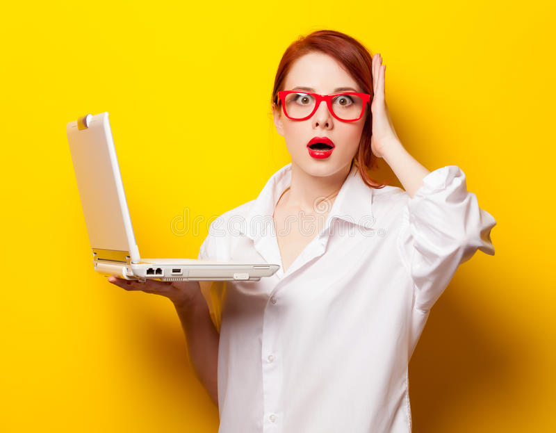 Förvånad rödhårig manflicka i den vita skjortan med datoren royaltyfria foton