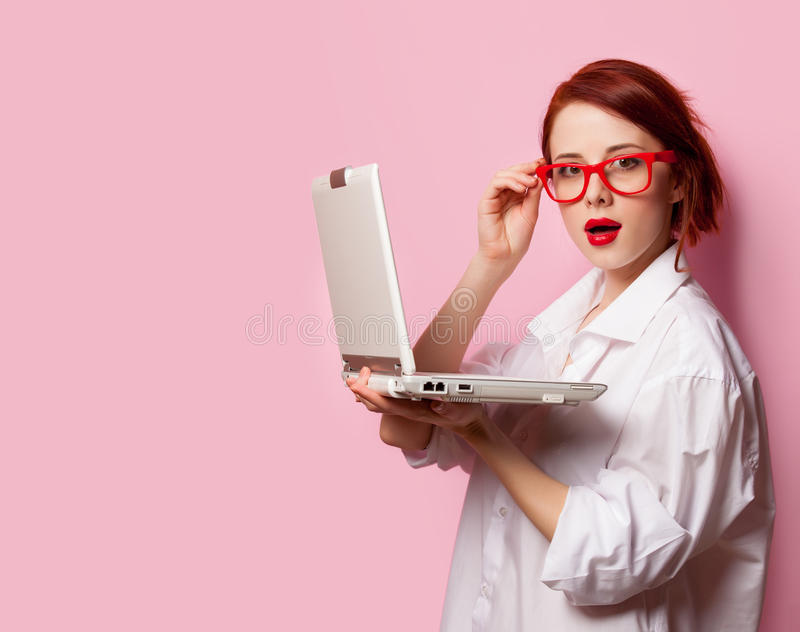 Förvånad rödhårig manflicka i den vita skjortan med datoren arkivfoton
