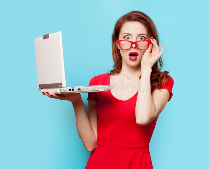 Förvånad rödhårig manflicka med bärbara datorn royaltyfri bild