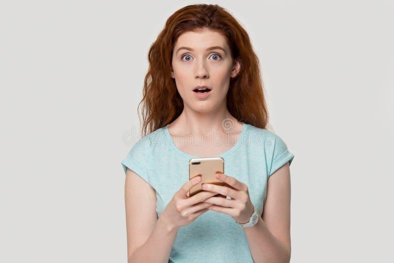 Förvånad rödhårig mankvinna som chockas av textmeddelandet på cellen royaltyfri fotografi