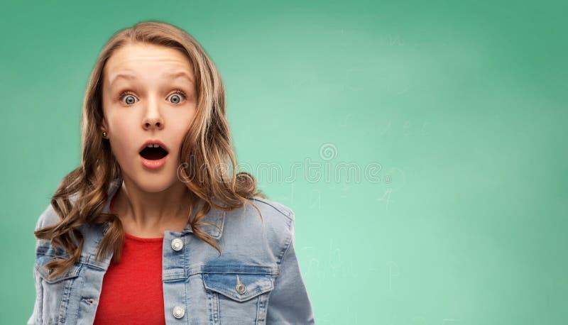 Förvånad studentflicka över grön bakgrund royaltyfri foto
