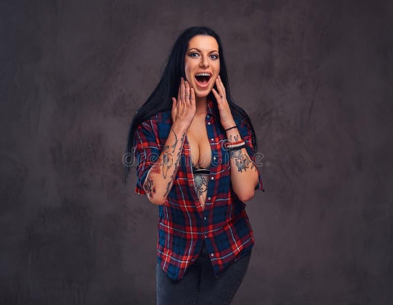 Förvånad tatuerad flicka som bär en röd knäppt upp kontrollerad skjorta fotografering för bildbyråer