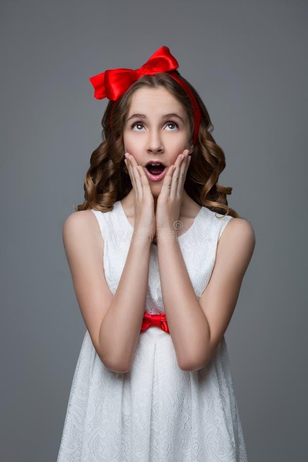 Förvånad tonårig flicka med den röda pilbågen på huvudet royaltyfri bild