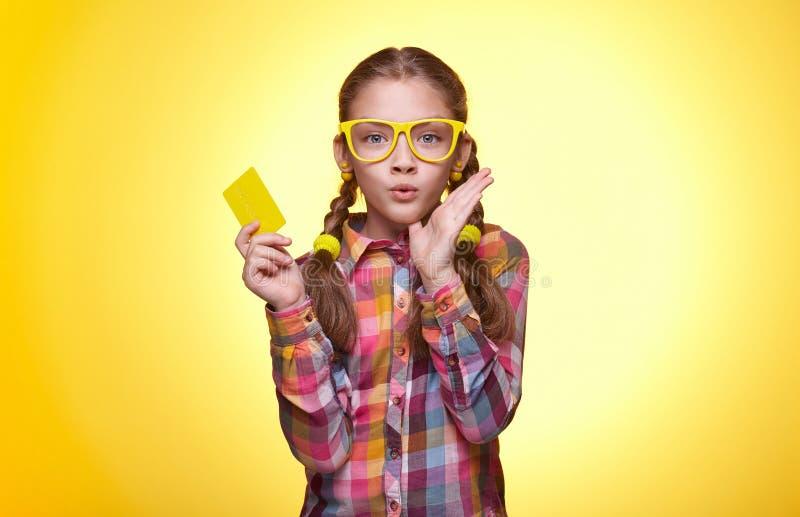 Förvånad tonårig flicka med kreditkorten över gul bakgrund arkivfoton
