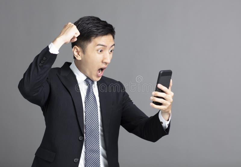 Förvånad ung affärsman som håller ögonen på mobiltelefonen arkivbild