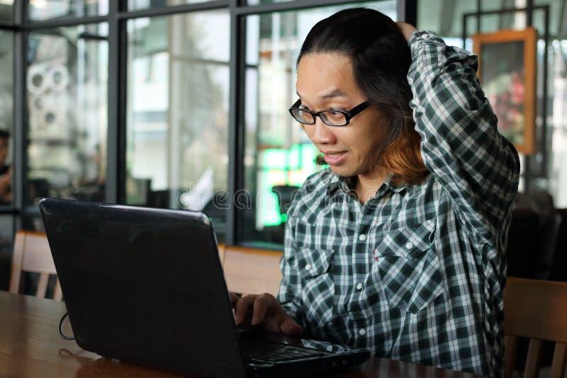 Förvånad ung asiatisk affärsman med bärbara datorn i regeringsställning Utmattad och överansträngningjobbbegrepp royaltyfri foto