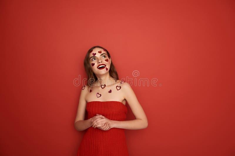 F?rv?nad ung dam med dekorativa hj?rtor p? kroppen som inomhus ser upp arkivfoto