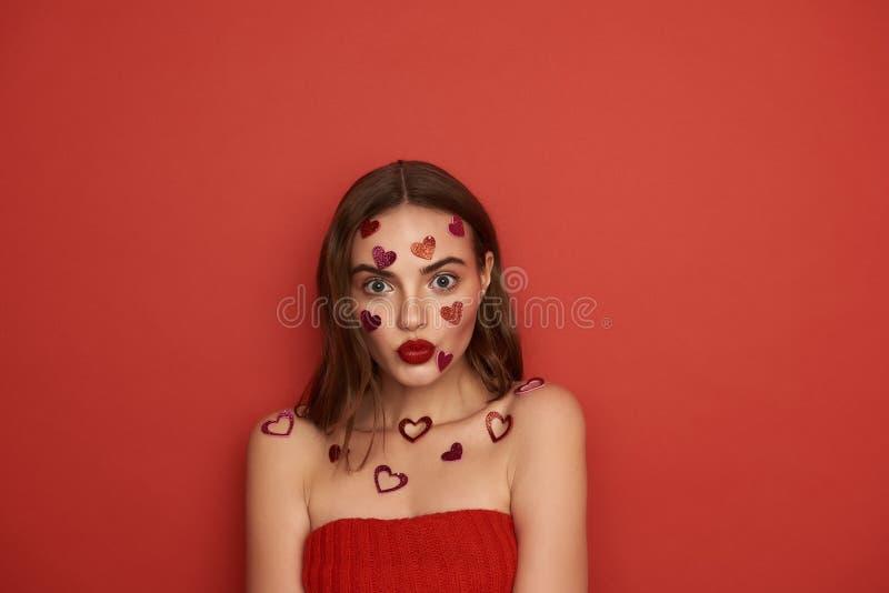 F?rv?nad ung dam med dekorativa hj?rtor p? kroppen som inomhus trutar hennes kanter royaltyfri foto