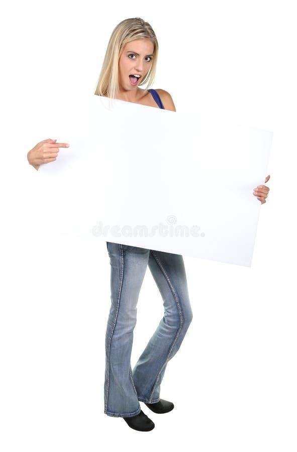 Förvånad ung dam med teckenbrädet royaltyfri foto