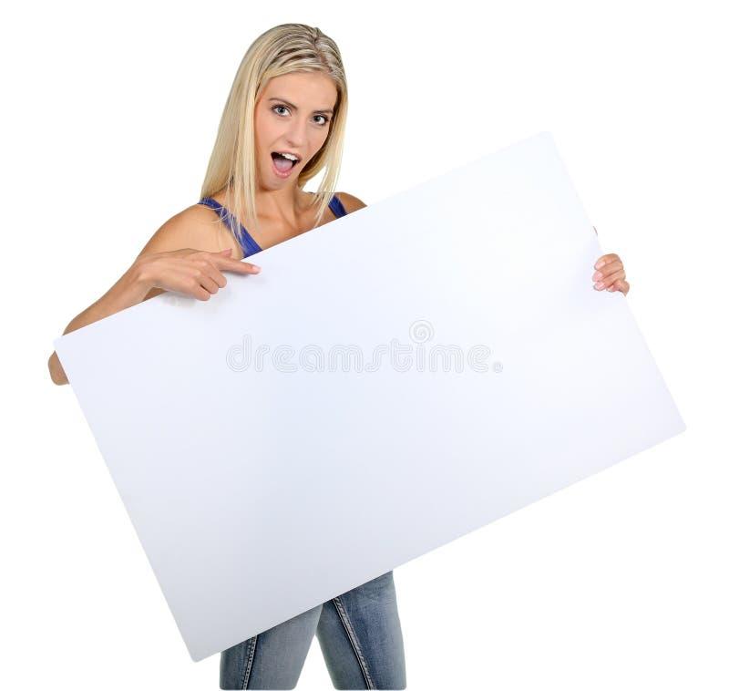 Förvånad ung dam med teckenbrädet arkivbild
