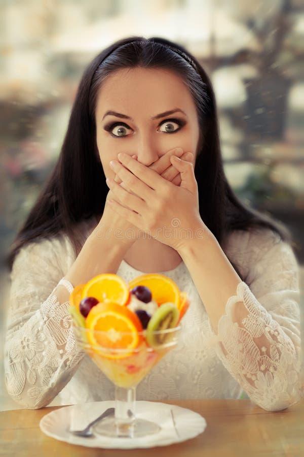 Förvånad ung kvinna med efterrätten för fruktsallad fotografering för bildbyråer