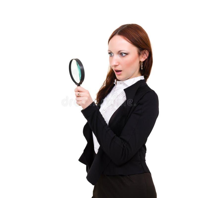 Förvånad ung kvinna med förstoringsglaset royaltyfria bilder
