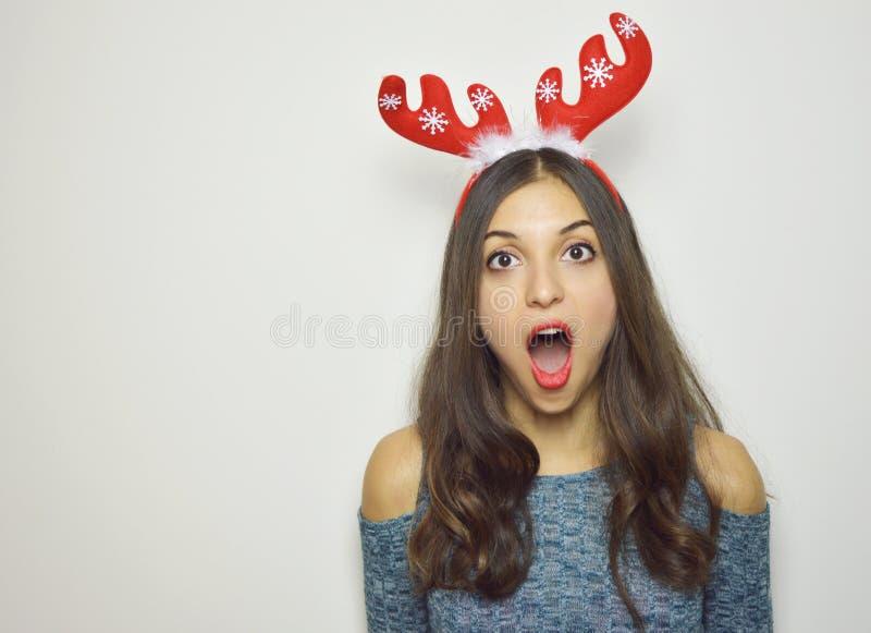Förvånad ung kvinna med renhorn på hennes huvud med munnen som är öppen på vit bakgrund arkivfoton