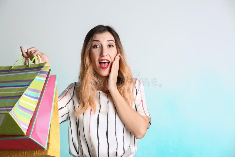 Förvånad ung kvinna med shoppingpåsar på ljus bakgrund royaltyfri bild
