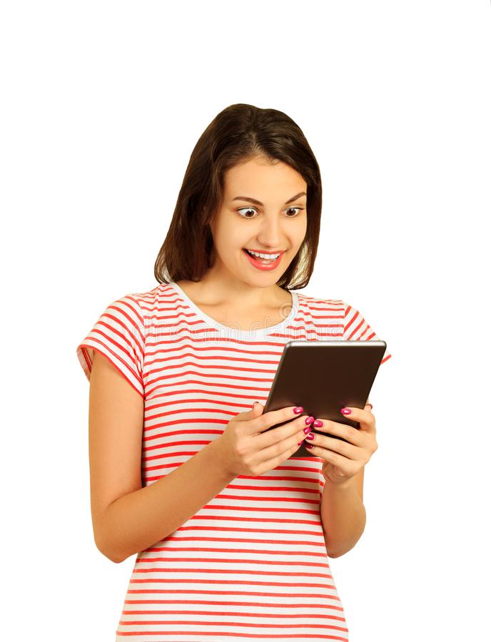 Förvånad ung kvinna som bär röd randig kläder genom att använda en minnestavlaPC emotionell flicka som isoleras på vit bakgrund royaltyfri fotografi