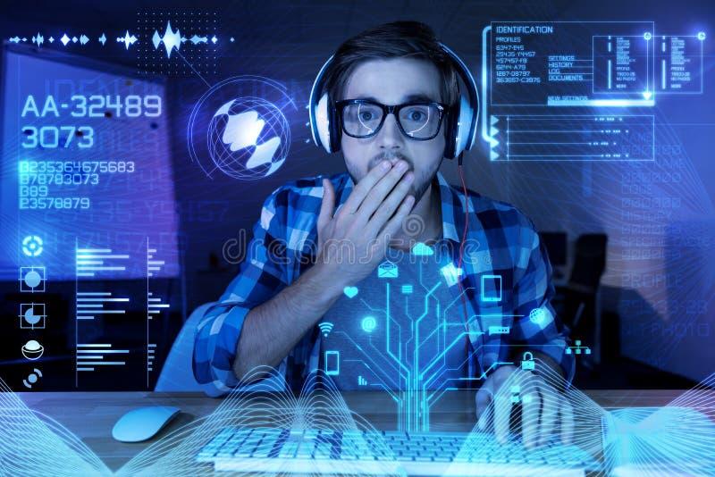 Förvånad ung programmerare som ser skärmen och stänger hans mun royaltyfri fotografi